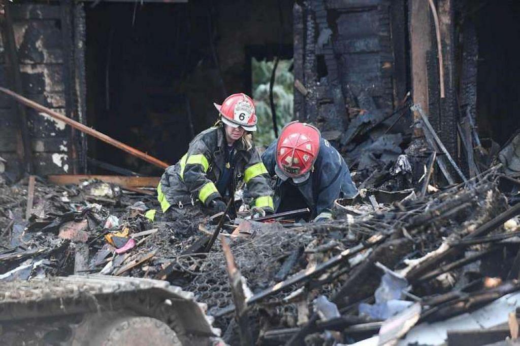Anggota bomba mencari di puing rumah tiga tingkat di Baltimore, Maryland, yang dijilat api, menyebabkan enam kanak-kanak adik-beradik terbunuh dan ibu serta tiga lagi adik-beradik mereka cedera.