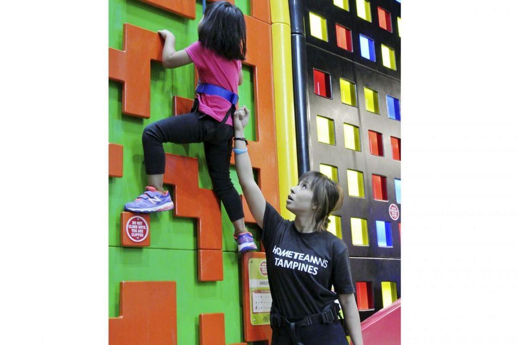 SESUAI UNTUK SEMUA LAPISAN USIA: Ketua spesialis permainan tarikan baru Clip n' Climb, Cik Nazatul Syima Abd Ghani (kanan) kelihatan sedang membantu seorang kanak-kanak berusia lima tahun memanjat salah satu tembok bertema setinggi lapan meter. - Foto NURMAYA ALIAS