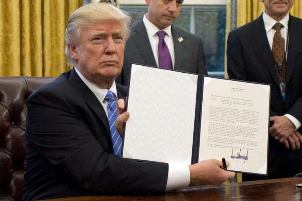 Presiden Amerika Syarikat Donald Trump menunjukkan Arahan Eksekutif mengeluarkan Amerika daripada Perkongsian Trans-Pasifik (TPP) selepas menurunkan tandatangan di Pejabatnya di Rumah Putih, Washington, DC, pada 23 Jan 2017.