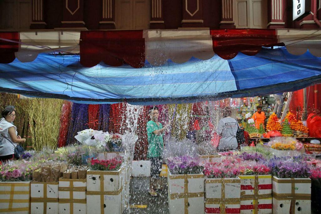JUALAN MURAM: Seorang peniaga di Temple Street sedang membuang air hujan yang terkumpul di khemahnya ekoran hujan lebat. – Foto THE STRAITS TIMES