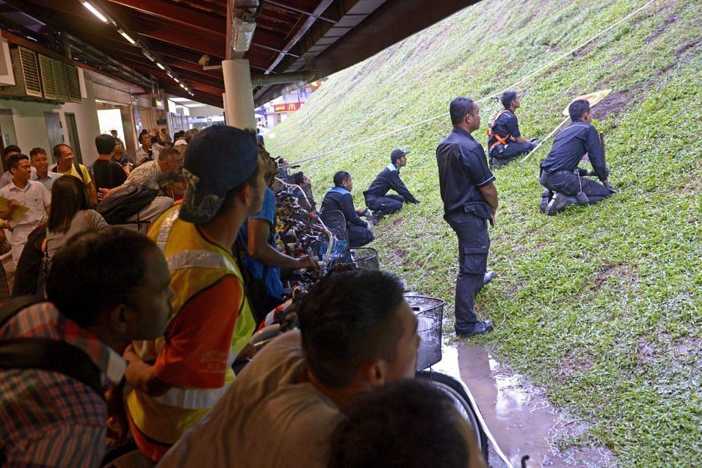 Pekerja syarikat pembunuh serangga Star Pest Control berusaha menghapuskan tikus dan lubang tikus dekat stesen MRT Bukit Batok pada 18 December 2014.