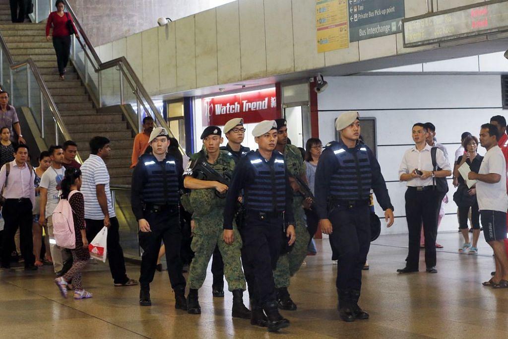 Pegawai polis Komand Keselamatan Pengangkutan Awam dan askar Angkatan Bersenjata Singapura (SAF) meronda di stesen MRT Jurong East pada waktu sibuk petang pada Oktober 2016.