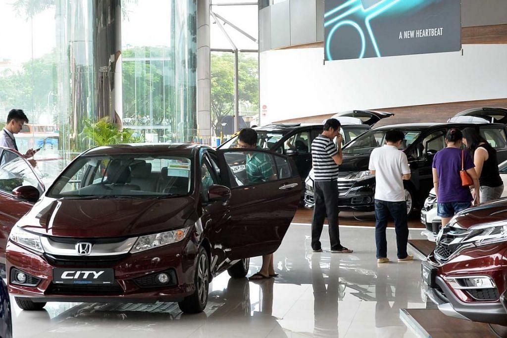 Bakal pembeli melihat-lihat kereta di bilik pameran Kah Motor Singapore, pengedar kereta Honda, tahun lalu (2016).