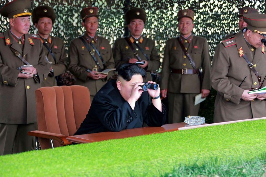 Gambar tidak bertarikh yang dikeluarkan oleh agensi berita rasmi Korea Utara, Korean Central News Agency  (KCNA) pada 19 November 2016 ini menunjukkan pemimpin Korea Utara, Encik Kim Jong-Un, memeriksa satu pertandingan menembak bagi penembak wanita sistem roket aneka  pelancaran (MLRS) di sebuah lokasi rahsia.