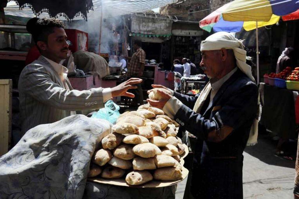 Seorang penjaja menjual roti di sebuah pasar di bandar lama Sana'a, Yaman.