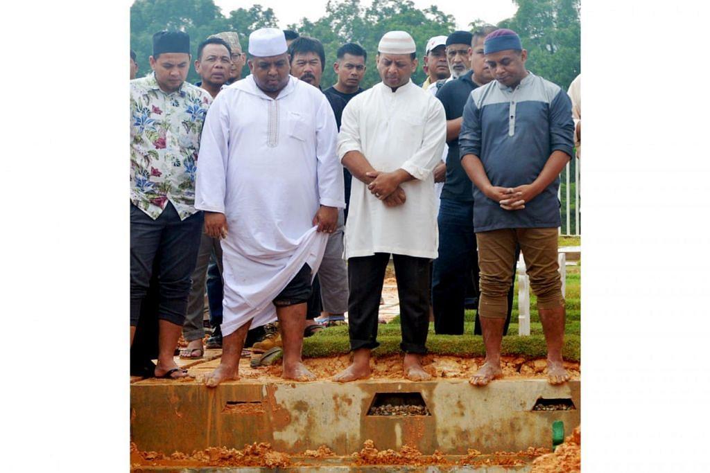 SELAMAT DIKEBUMIKAN: Anak-anak Allahyarham M Ishak, (barisan depan, dua dari kiri) Encik Mohd Nazaruddin, Encik Shahbudin dan Encik Masjuri, bersama keluarga dan teman Allahyarham hadir di Pusara Aman semalam. – Foto KHALID BABA