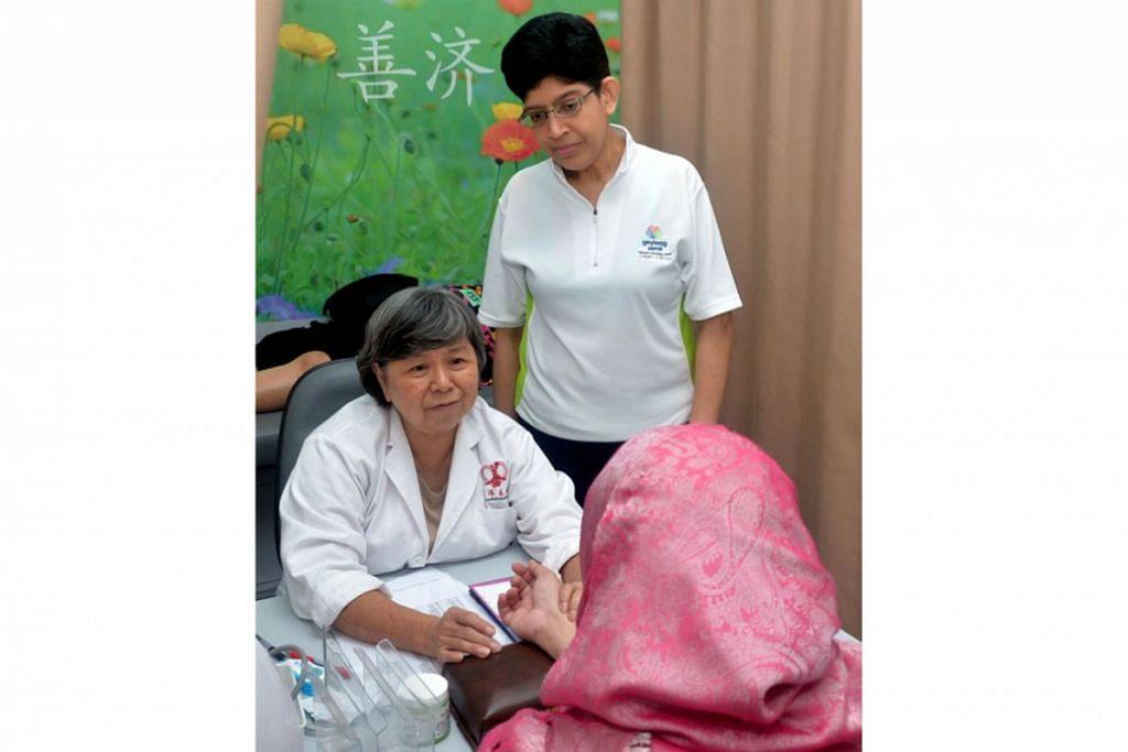 RAWAT CARA TRADISIONAL: Dr Fatimah (berdiri) mengunjungi klinik perubatan tradisional Cina di Geylang Road yang merawat pesakit pelbagai kaum yang menghadapi isu kesihatan mental dan penyakit lain. - Foto KHALID BABA
