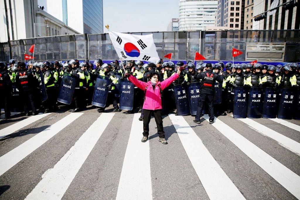 KEMELUT POLITIK BERTERUSAN: Seorang penyokong Cik Park berdiri di depan pasukan keselamatan sebelum satu rapat bagi menyokong bekas Presiden Korea Selatan itu diadakan di Seoul semalam. - Foto REUTERS