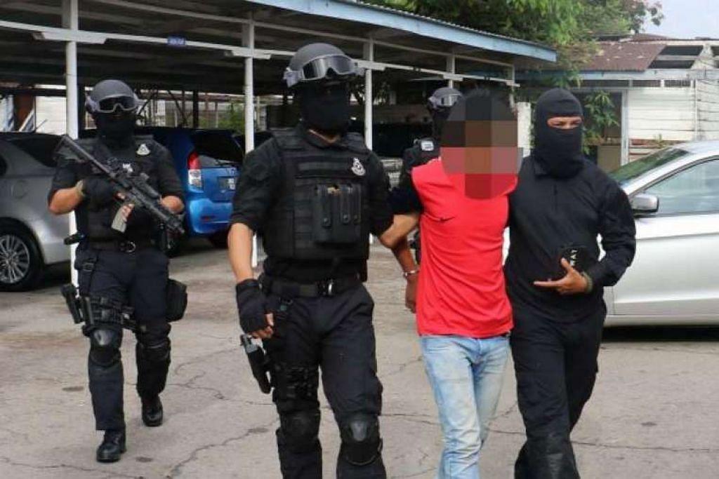 Pegawai Bahagian Banteras Pengganasan Cawangan Khas Malaysia menahan salah seorang daripada tujuh suspek.