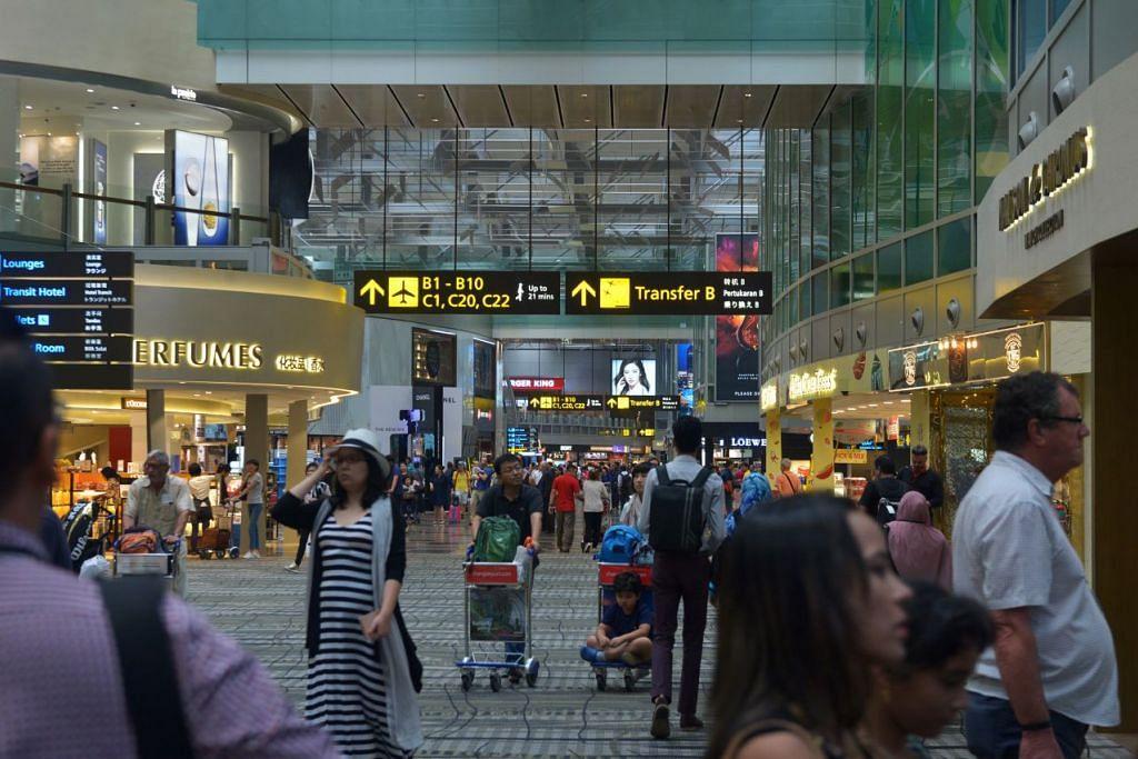 Pelancong melalui kawasan beli-belah bebas cukai di ruang transit di Terminal 3 Lapangan Terbang Changi.
