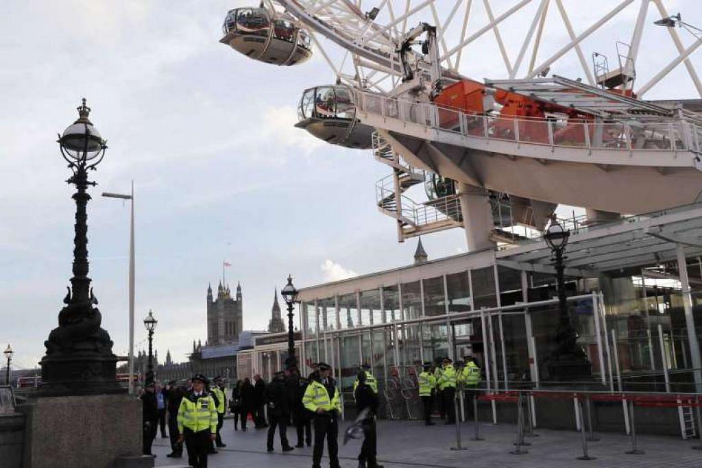 Pegawai polis berkawal di pintu keluar tempat riadah 'London Eye' selepas ia dihentikan berikutan serangan di Westminster Bridge di London, Britain.