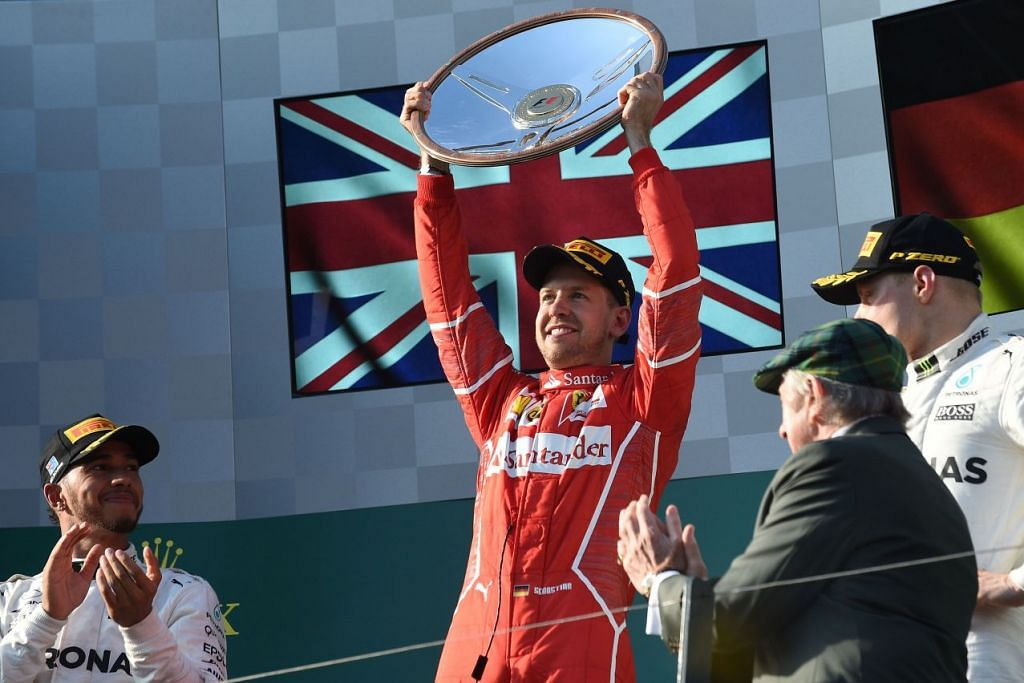 Sebastian Vettel menjulang trofi selepas memenangi perlumbaan Formula Satu Grand Prix Australia di Melbourne pada 26 Mac 2017, sedang naib juara Lewis Hamilton (kiri) dan pemenang tempat ketiga, Valtteri Bottas (kanan), menyaksikannya.