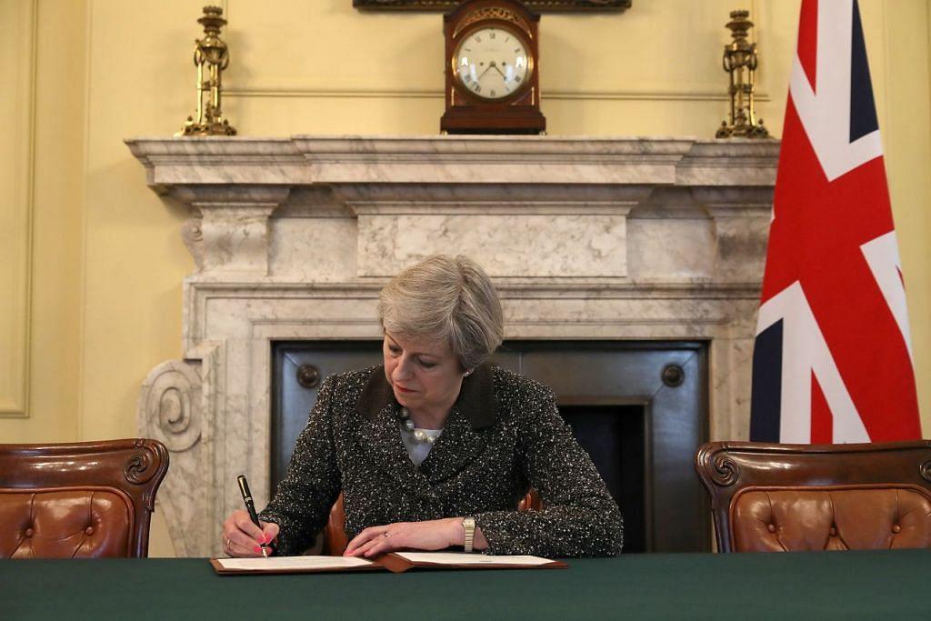 RASMI PERPISAHAN: Perdana Menteri Britain, Cik Theresa May, menandatangani surat bersejarah yang akan dengan rasminya memulakan proses Brexit untuk Britain keluar dari Kesatuan Eropah. - Foto: REUTERS