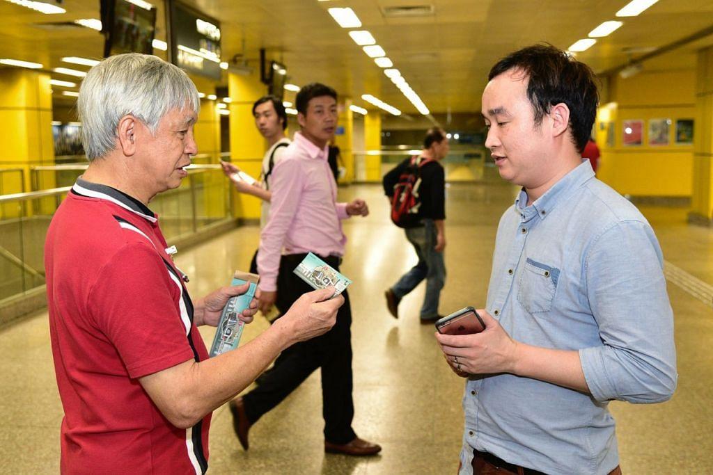 TANDA MUHIBAH: Kakitangan SMRT mengedarkan tiket kereta api percuma di semua stesen Laluan Utara-Selatan bermula 10.30 malam kelmarin memandangkan khidmat MRT yang mereka naiki bakal mengalami sedikit kegenjotan. - Foto THE STRAITS TIMES