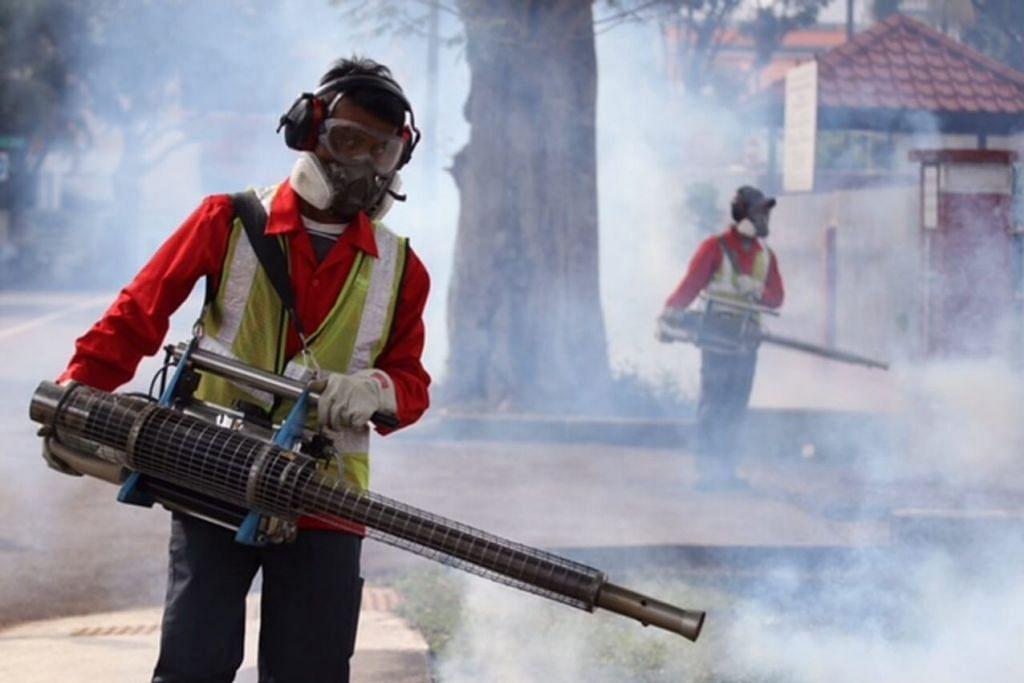 HAPUSKAN PEMBIAKAN NYAMUK: Pengendali kawalan serangga perosak melakukan pengkabutan di kawasan Simon Place pagi tadi selepas kes Zika disahkan berlaku di kawasan itu. - Foto THE STRAITS TIMES