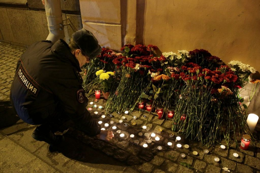 DIRUDUNG HIBA: Seorang anggota polis meletakkan jambangan bunga sebagai memperingati mangsa serangan ganas di luar stesen Institut Tekhnologicheskiy di laluan keretapi metro St. Petersburg. - Foto REUTERS