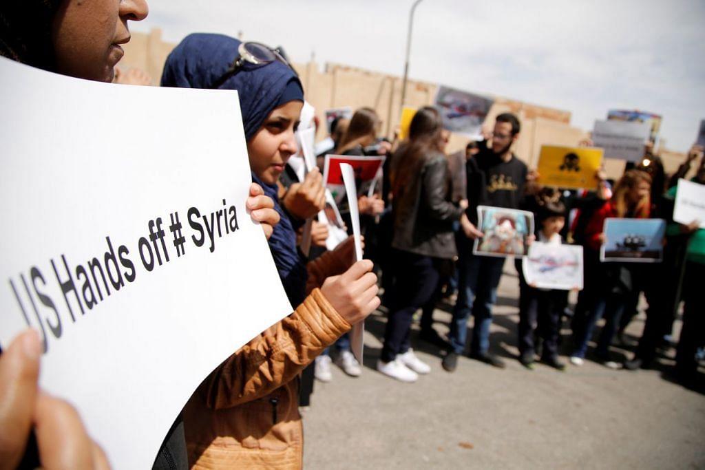 TOLAK CAMPUR TANGAN: Rakyat Syria membuat bantahan terhadap tindakan Amerika Syarikat menyerang negara itu di depan bangunan Pertubuhan Bangsa-Bangsa Bersatu di Damsyik, ibu kota Syria, pada 8 April lalu. - Foto REUTERS