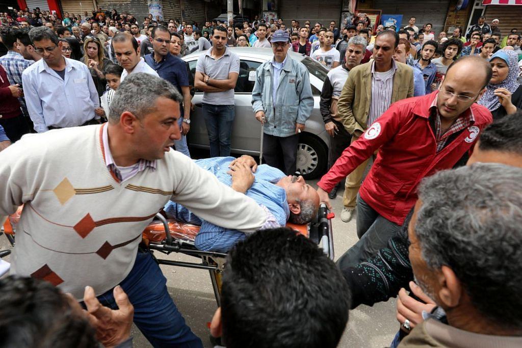 MENGUSUNG MANGSA: Seorang mangsa dikejarkan ke ambulan selepas sebutir bom meletup di di Gereja Koptik di Tanta, Mesir pada 8 April lalu. - Foto REUTERS
