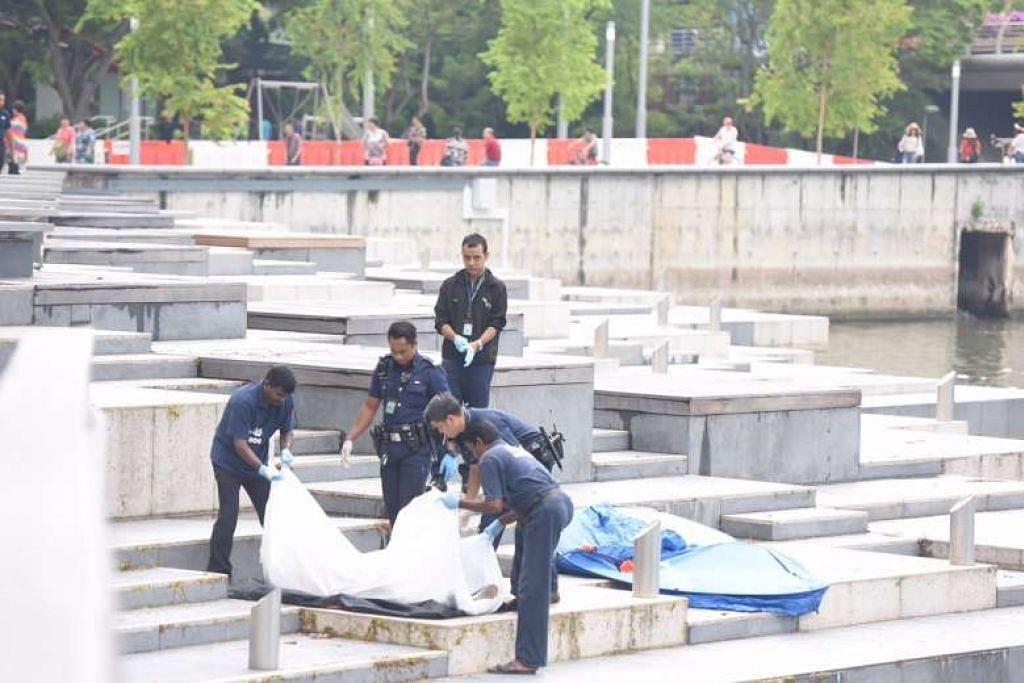 PENEMUAN MAYAT: Anggota polis mengangkat sekujur mayat yang ditemui di Sungai Singapura pagi tadi. - Foto THE STRAITS TIMES