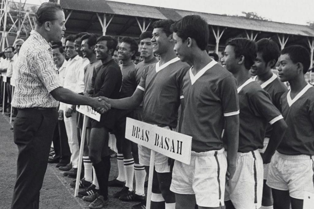 PENGGEMAR SUKAN: Sebagai Menteri yang bertanggungjawab bagi Sukan, Encik Othman bersalam dengan beberapa peserta di acara pembukaan kejohanan bola sepak antara kawasan undi di Stadium Jalan Besar.