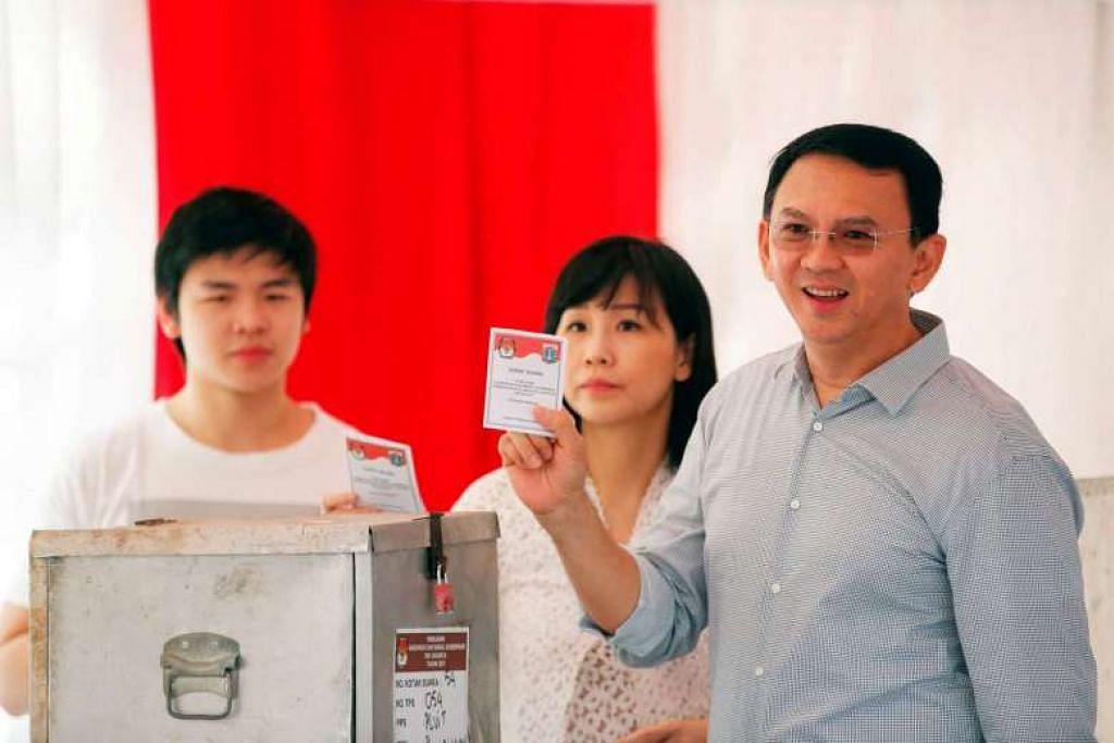 MELAKSANAKAN TANGGUNGJAWAB: Gabenor Jakarta, Encik Basuki Tjahaja Purnama atau lebih dikenali sebagai 'Ahok' (kanan) bersama isterinya, Cik Veronika Tan, dan anak sulung mereka, Nicholas Sean Purnama, mengundi berdekatan rumah mereka bagi pilihan raya untuk memilih Gabenor dan Naib Gabenor Jakarta. - Foto REUTERS