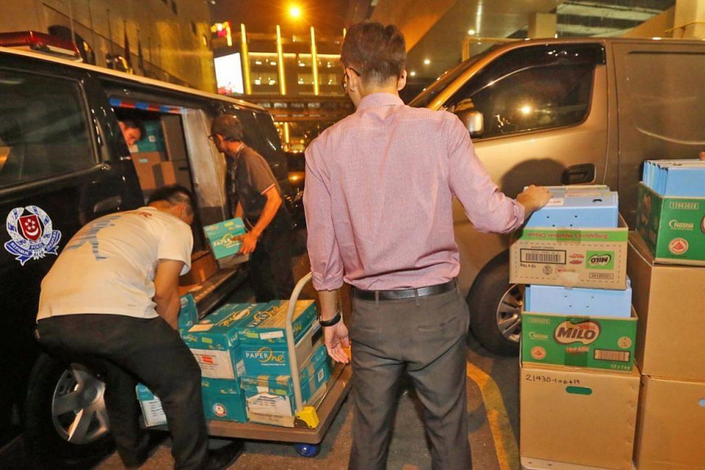 SIASATAN BERTERUSAN: Kotak dibawa keluar oleh pegawai CAD dari pejabat Kelab Bola Sepak Tiong Bahru kelmarin. -  Foto THE STRAITS TIMES