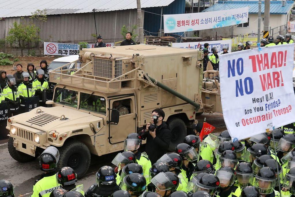 DIBANTAH: Pasukan antirusuhan Korea Selatan mengepung tepi jalan raya Seongju awal semalam bagi menghalang penunjuk perasaan membaling botol air ke arah treler yang membawa sistem pertahanan antipeluru berpandu Amerika di situ. - Foto AFP