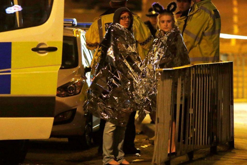Dua wanita berselubung selimut berdiri di luar Manchester Arena.