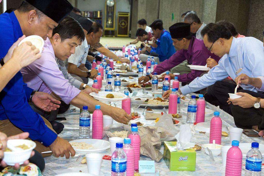 ERATKAN HUBUNGAN: (Dari kiri) Encik Abdul Rahim dan Encik Tan bersama beberapa undangan menjamu selera semasa majlis iftar di Masjid Darul Aman. – Foto SIX5 PRODUCTIONS LLP
