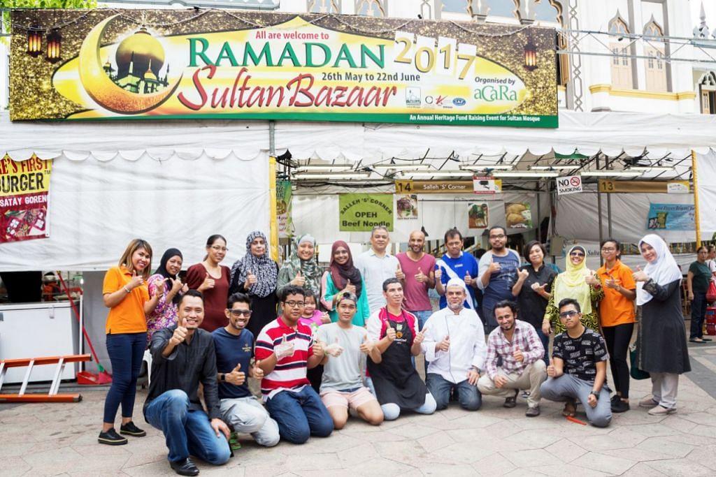 BAZAR SEMAKIN SELESA DAN BERSIH: Encik Muhammad Ali (bertinggung, paling kiri) bergambar bersama para pegerai lain di depan bazar Raya yang terletak di depan Masjid Sultan di Arab Street. – Foto ZALEHA ABDUL KADER