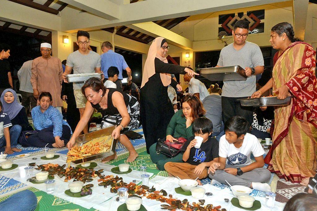 'KENDURI' MAKANAN LAUT: Cik Noreeni (bertudung di tengah) menganjurkan sesi iftar 'shell-out' bagi merapatkan hubungan bersama keluarga, jiran dan teman termasuk yang bukan beragama Islam. - Foto KHALID BABA