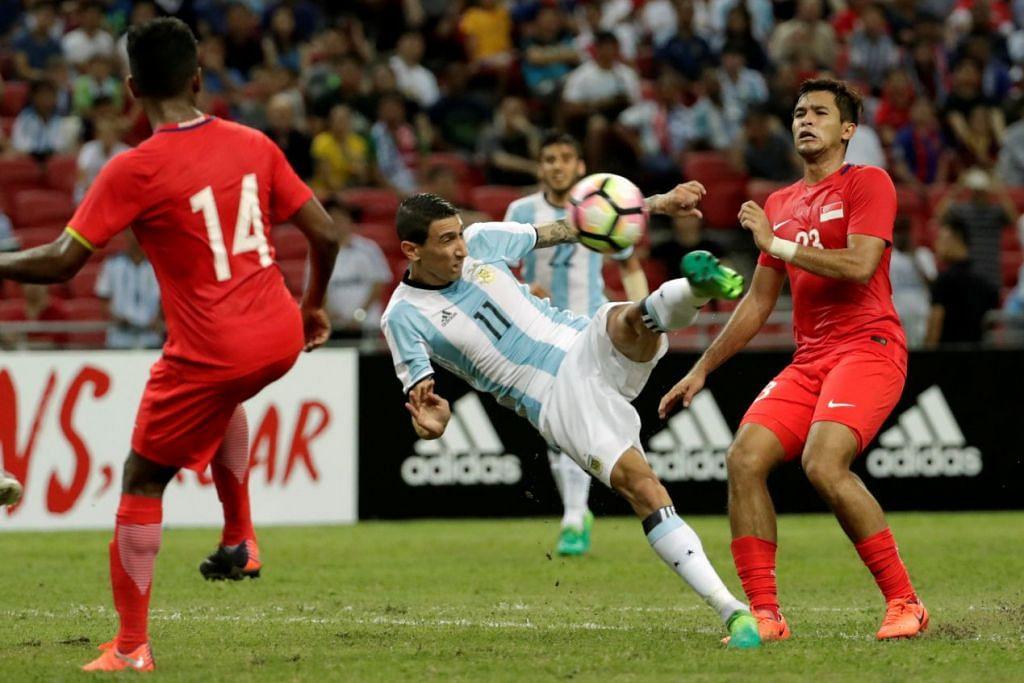 Pemain Argentina, Angel Di Maria dan pemain Singapura Zulfahmi Arifin beraksi semasa perlawanan malam Selasa.   Foto: Reuters