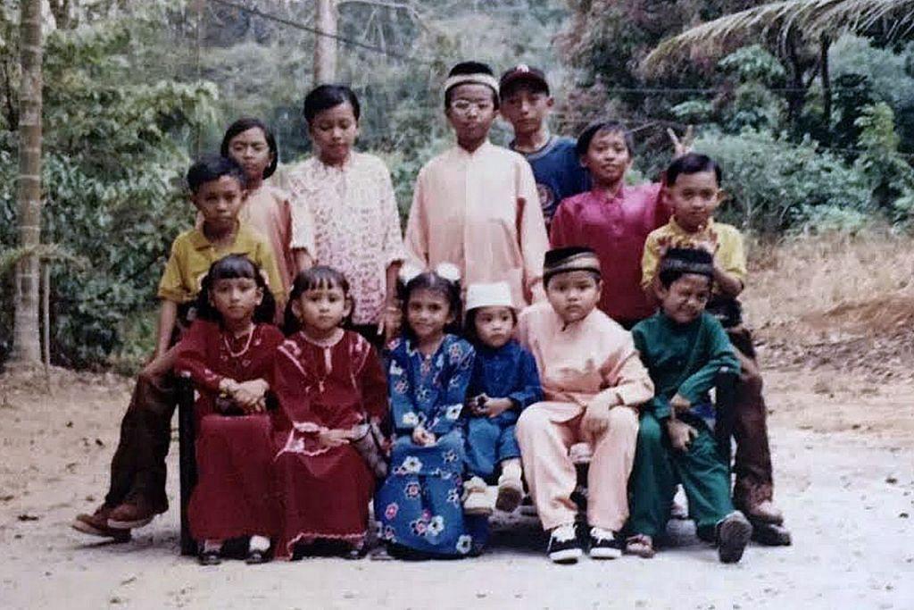 Cik Yusrina (berdiri, paling kiri) bersama saudara-maranya bergambar di kampung mereka di Pulau Ubin pada zaman 1990-an.