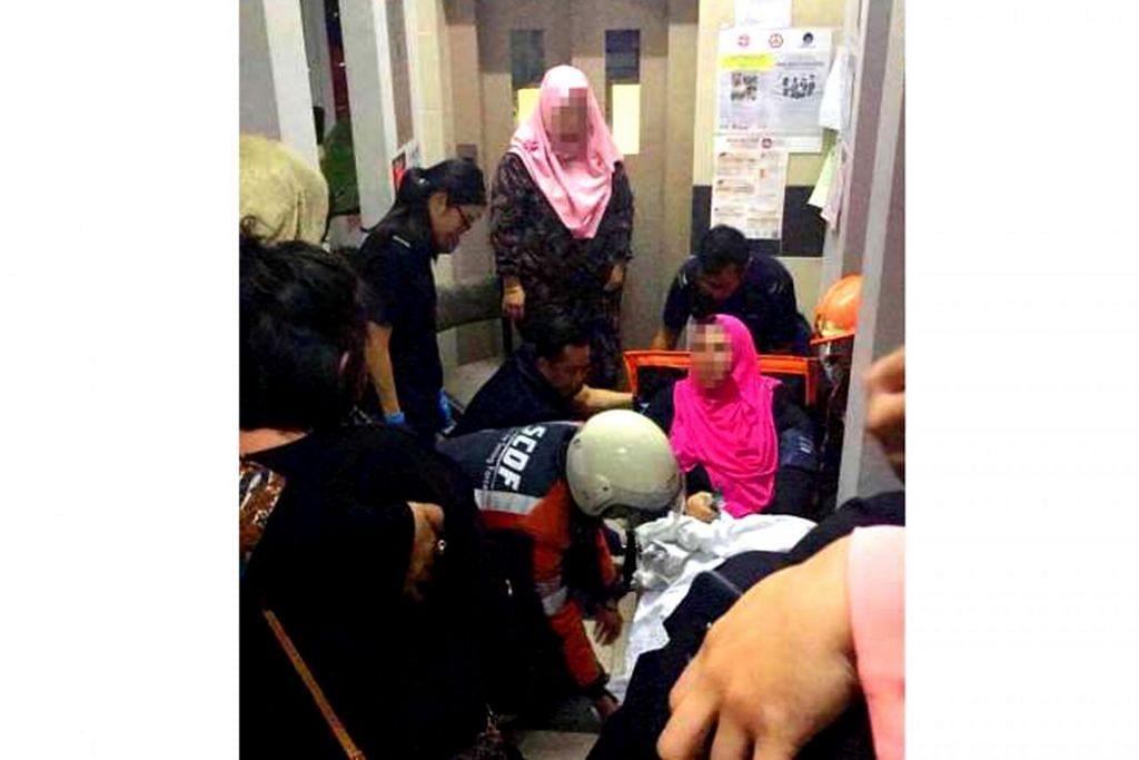 KAKI RETAK: Cik Fauziah dibantu pegawai Pasukan Pertahanan Awam Singapura (SCDF) kerana kakinya retak apabila lif di Blok 542 Jurong West Avenue 1 tiba-tiba menjunam empat tingkat. – Foto fail