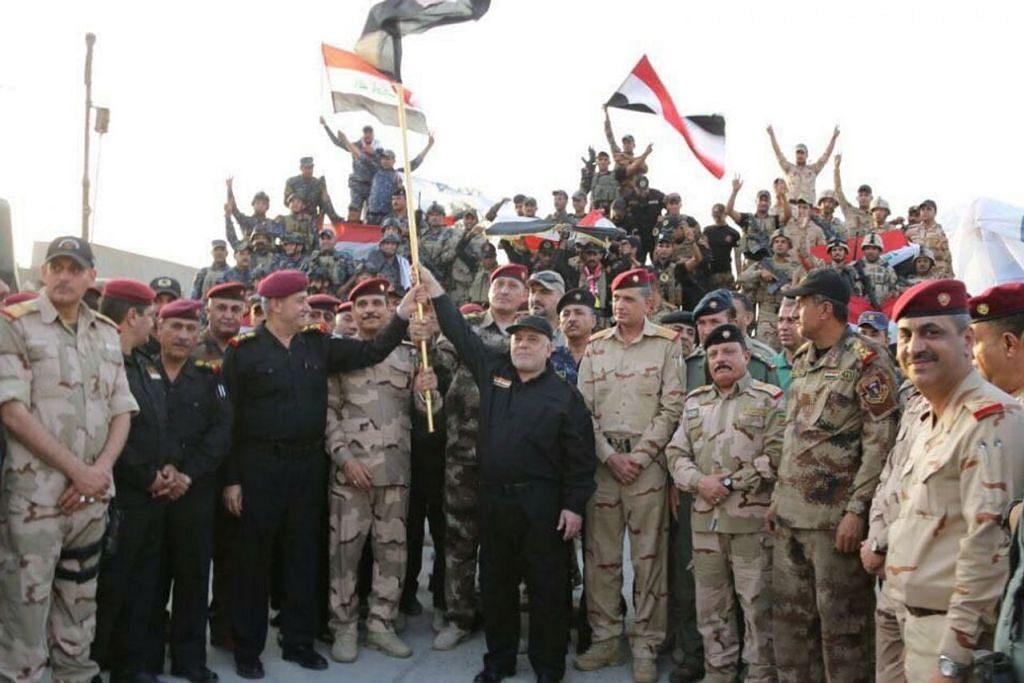 MOSUL – SELEPAS ISIS DITUMPASKAN - ISYTIHAR KEMENANGAN: Perdana Menteri Iraq Haider al-Abadi (tengah) mengangkat bendera Iraq sedang beliau mengumum kemenangan menumpas kumpulan militan IS di Mosul, Iraq, pada 10 Julai lalu. - Foto REUTERS