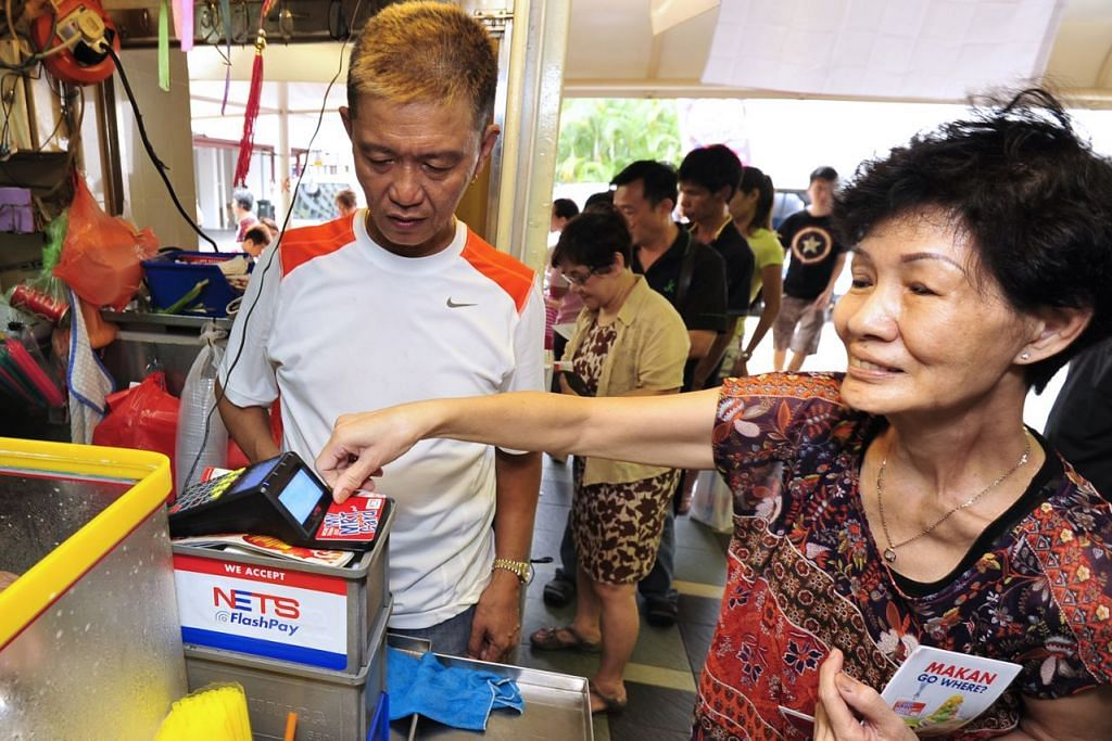 BAYARAN TANPA TUNAI: Seorang pelanggan warga emas membayar minuman dengan mengimbas kad menggunakan FlashPay di pasar Beo Crescent. - Foto fail