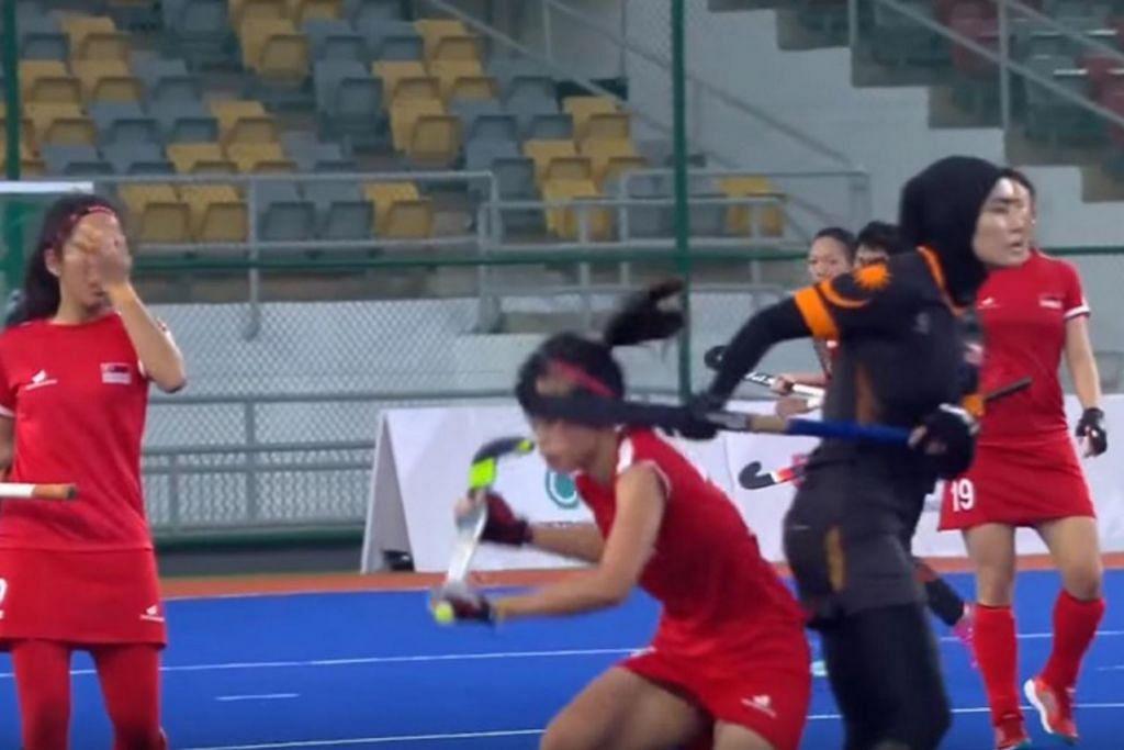KAYU HOKI TERKENA KE MUKA: Pemain Malaysia kelihatan seperti telah menghayunkan kayu hokinya ke arah muka Syaheeza. Mujur Syaheeza tidak mengalami kecederaan dan lalu meneruskan perlawanan di mana Singapura tewas 5-0. - Foto SINGSOC