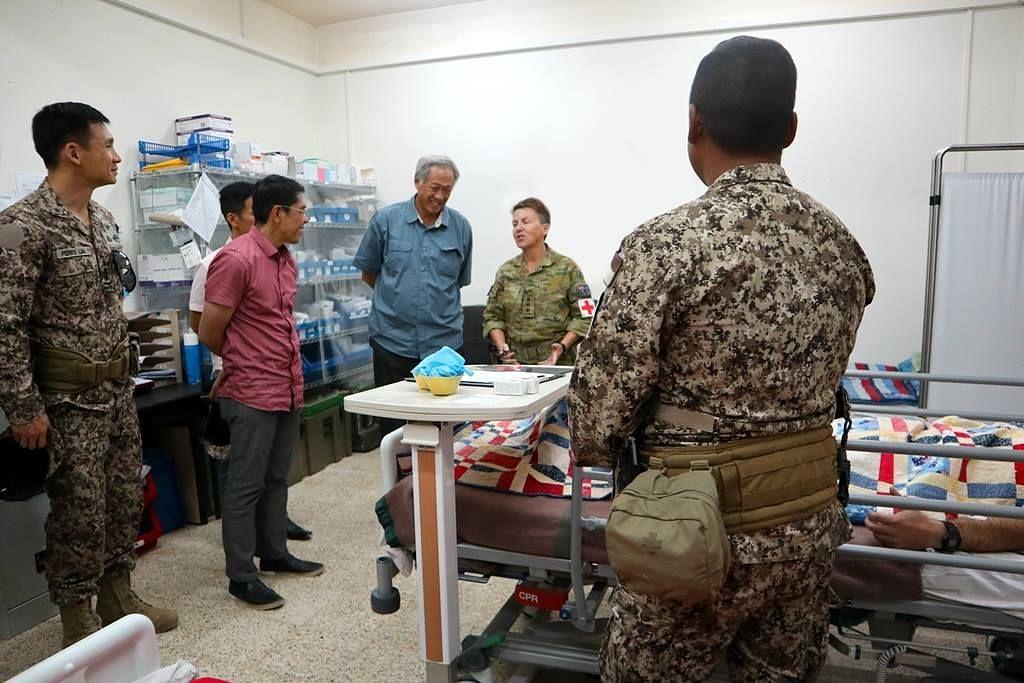 KUNJUNGAN ISTIMEWA: Dr Ng (baju biru) dan Dr Maliki berbual-bual dengan pasukan perubatan dari berbilang negeri semasa lawatan mereka ke Iraq.