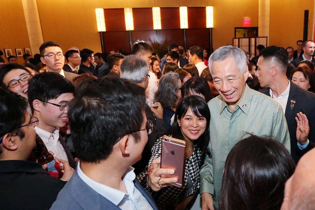 BERTEMU WARGA SINGAPURA: Encik Lee bergambar dengan warga Singapura yang tinggal di Washington dan kawasan sekitaran di jamuan khas yang diadakan di Kedutaan Singapura. - Foto THE STRAITS TIMES