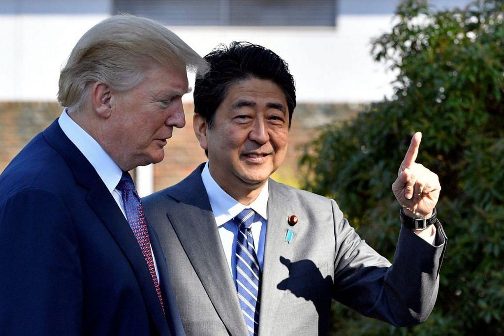 TETAMU ERHORMAT: Encik Abe (kanan) menyambut ketibaan Encik Trump, setibanya di Kelab Riadah Kasumigaseki Country Club Kawagoe, Tokyo.