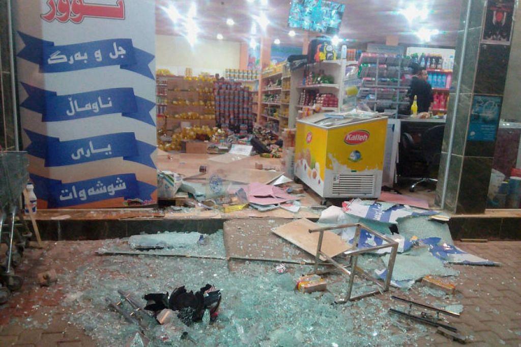KEROSAKAN TERUK: Tingkap kaca pecah di sebuah kedai serbaneka di Halabia, Iraq selepas gempa bumi. - Foto Reuters