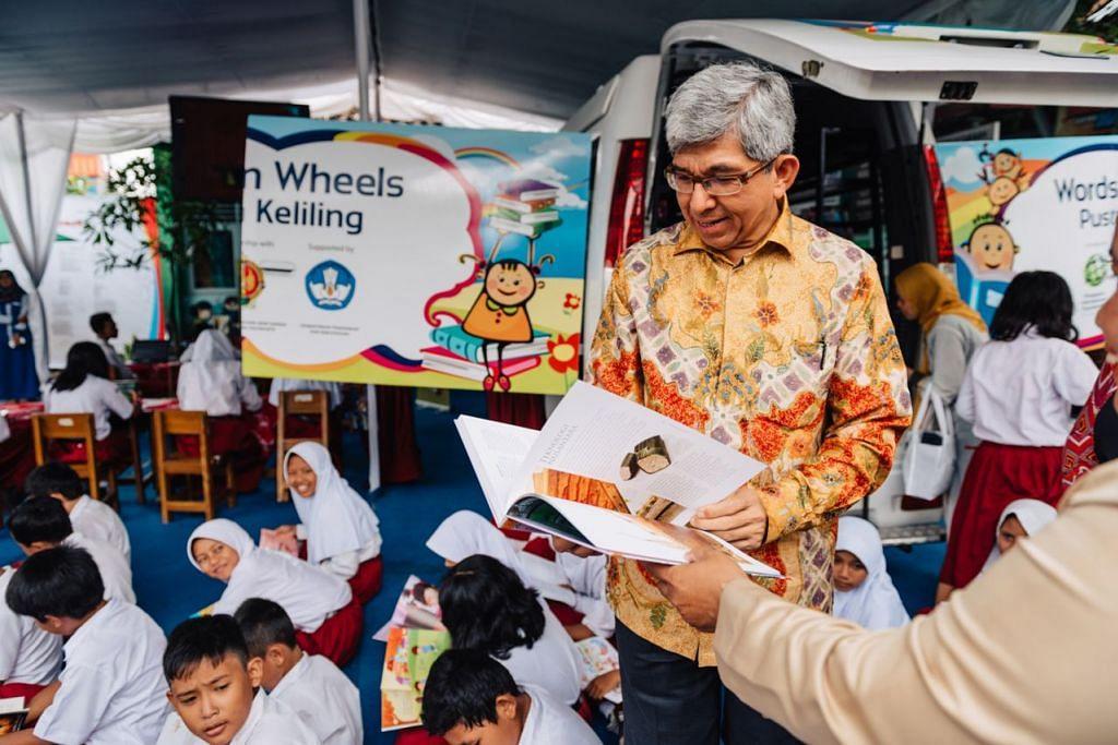 KONGSI ILMU: Dr Yaacob Ibrahim membaca salah satu daripada 2,000 buku yang ditawarkan perpustakaan bergerak untuk kanak-kanak di Yogyakarta. Perpustakaan itu disediakan SIF menerusi program WoW. - Foto SIF