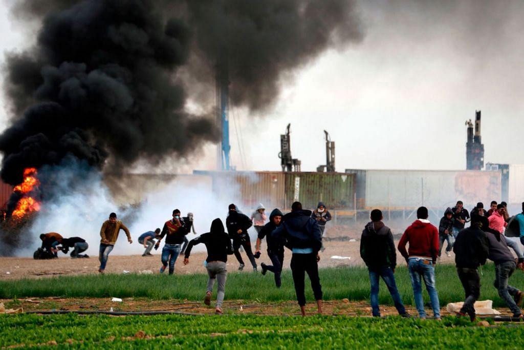 KEADAAN MASIH TEGANG: Penunjuk perasaan Palestin bertempur dengan askar Israel berdekatan sempadan Israel-Gaza, ke timur bandar Khan Yunis di Jaluran Gaza, kelmarin. - Foto AFP