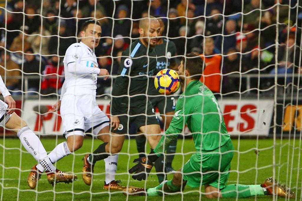 GOL KETIGA: Bintang midfield Manchester City, David Silva (jersi hitam depan), memperdaya penjaga gawang Swansea, Lukasz Fabianski, bagi menjaringkan gol ketiga pasukannya. – Foto AFP