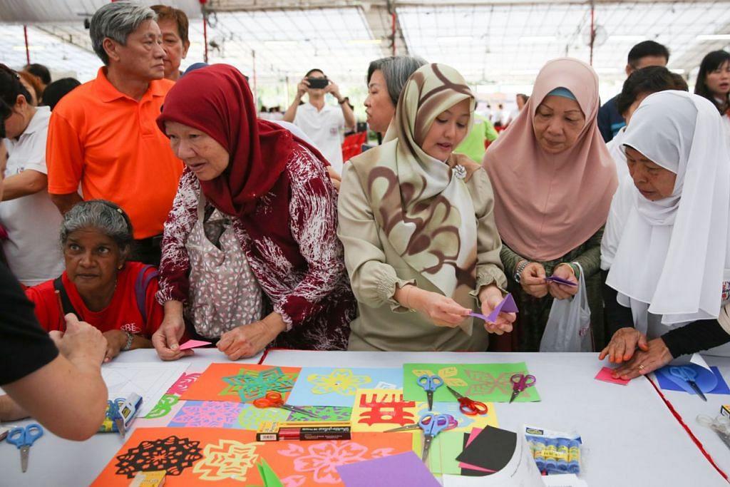 PELAJARI SENI HIASAN KERTAS WARNA CINA: Cik Rahayu (tiga dari kanan) mengongsi cara membuat potongan hiasan kertas warna dengan Cik Aminah Karnin (bertudung putih) dan Cik Sulinah Suri (di sebelahnya). Cik Zaleha Jaffar (bertudung merah) juga pelajari sama seni itu. - Foto BH oleh ONG WEE JIN