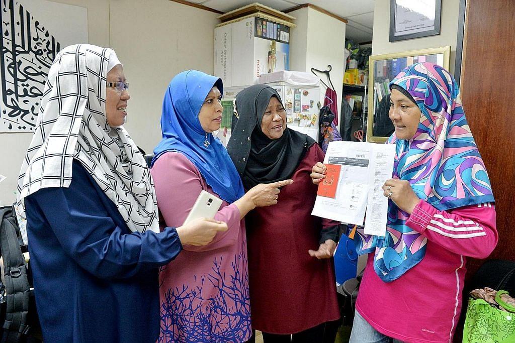 BANTU JEMAAH: Pegawai ejen De Hayat Travel and Services, Cik Kamisah Jani (kanan), sedang menunjukkan dokumen pengesahan biometrik kepada jemaah. - Foto BH oleh M.O. SALLEH