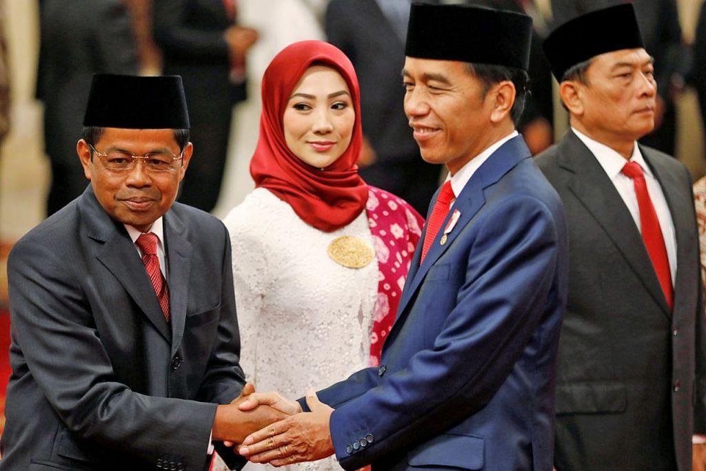 PELANTIKAN BARU: President Widodo (dua dari kanan) bersalaman dengan Encik Idrus (kiri) sambil disaksikan isterinya Cik Ridho Ekasari di majlis angkat sumpah anggota Kabinet baru di istana presiden di Jakarta semalam. Turut mengangkat sumpah di majlis itu ialah Jeneral Moeldoko (kanan). - Foto REUTERS