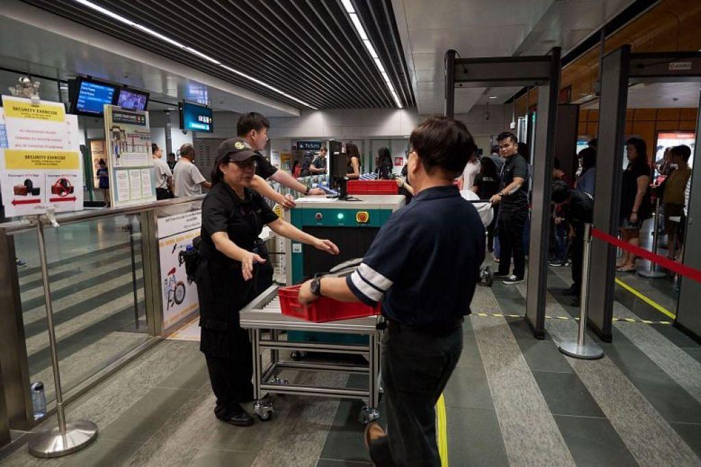 PEMERIKSAAN LEBIH KETAT: Penumpang meletak barangan mereka termasuk beg dan telefon bimbit untuk diimbas menggunakan mesin X-ray sebagai sebahagian satu latihan persiapan kecemasan di stesen Newton tadi.