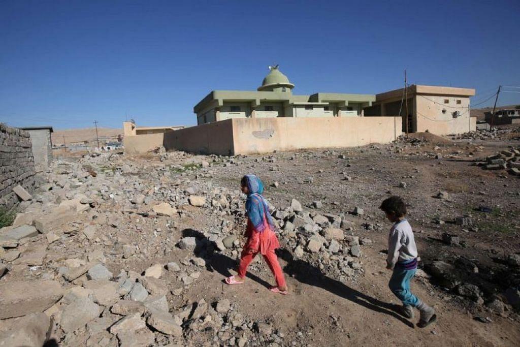 Kanak-kanak Iraq daripada masyarakat Shabak berjalan lewat rumah mereka, yang dimusnahkan oleh ISIS, di kampung Baz Gerkan dekat Mosul pada 10 Januari 2018.