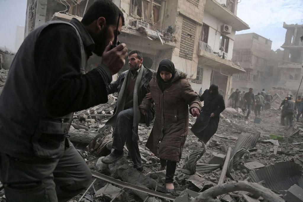 CARI PERLINDUNGAN: Penduduk di bandar Saqba, di Timur Ghouta, melarikan diri selepas kawasan itu musnah ekoran serangan udara kelmarin. - Foto AFP